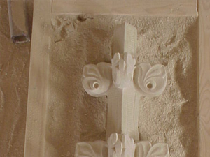 Carving details in a sand bed.